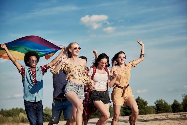 Glückliche freunde mit regenbogenfahne im freien laufen