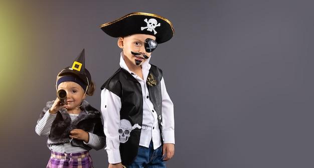 Glückliche freunde, piratenjunge und kleine hexe für halloween. fröhliche kinder bereit zu feiern.