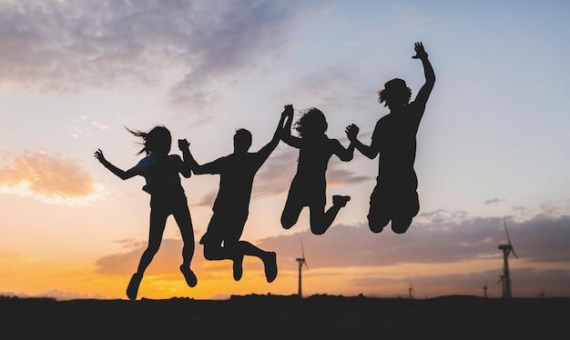 Glückliche freunde silhouetten springen auf sonnenuntergang
