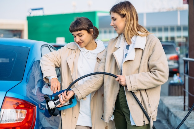 Glückliche freunde tanken auto in tankstelle. urlaubsreise von freunden