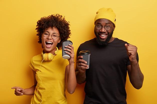 Glückliche freundin und freund bewegen sich aktiv, tanzen und haben spaß, trinken kaffee zum mitnehmen, tragen freizeitkleidung, verwenden stereokopfhörer, isoliert über gelber wand. menschen-, freizeit- und lifestyle-konzept