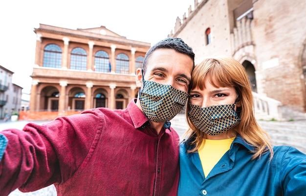Glückliche freundin und verliebter freund, die selfie nehmen, das durch gesichtsmaske bei altstadttour bedeckt wird