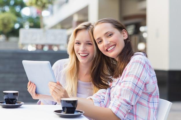 Glückliche freundinnen, die an der kamera lächeln und tablette halten