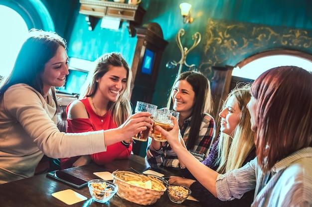 Glückliche freundinnen, die im brauerei-bar-restaurant auf bier anstoßen