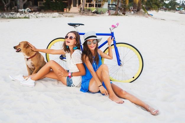 Glückliche freundinnen, die spaß am tropischen strand haben, frauen, die im urlaub in thailand mit dem fahrrad reisen