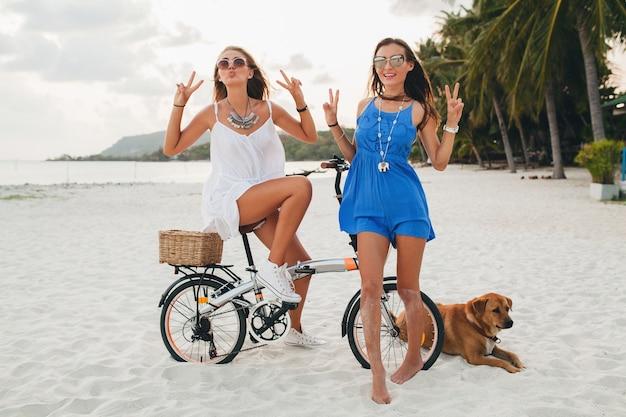 Glückliche freundinnen, die spaß am tropischen strand haben