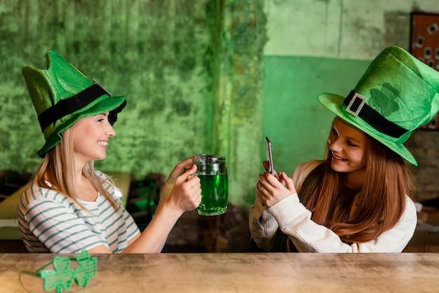 Glückliche freundinnen feiern st. patrick's tag zusammen an der bar mit einem drink