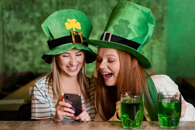 Glückliche freundinnen feiern st. patrick's tag zusammen an der bar mit smartphone