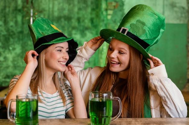 Glückliche freundinnen feiern st. patricks gemeinsamer tag an der bar