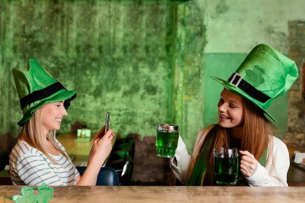Glückliche freundinnen feiern st. patricks tag zusammen mit getränken und smartphone