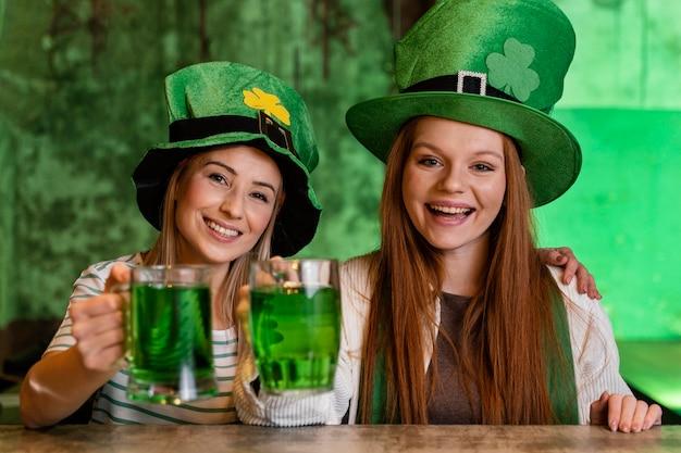 Glückliche freundinnen feiern st. patricks tag zusammen mit getränken
