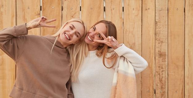 Glückliche freundinnen lächeln und gestikulieren v-zeichen