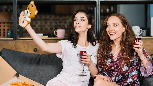 Glückliche freundinnen mit den getränken, die selfie auf mobiltelefon nehmen