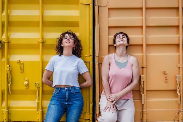 Glückliche freundinnen mit geschlossenen augen genießen im freien über gelbem hintergrund. sommerzeit. outdoor-lifestyle