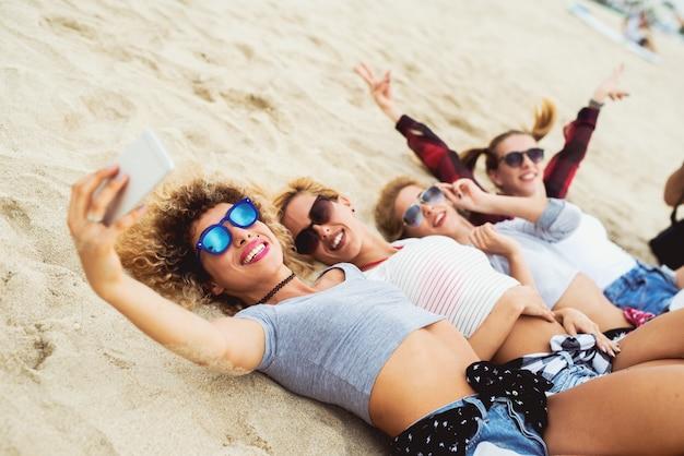 Glückliche freundinnen nehmen selfies, die auf sand liegen. trendiges sommeroutfit.