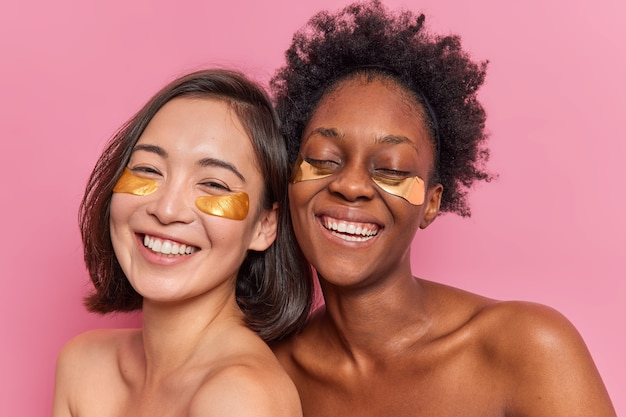 Glückliche freundinnen tragen goldene kollagenpflaster unter den augen auf, um dunkle ringe zu entfernen, gute laune zu haben, ohne hemd zu stehen, haben einen anderen hautzustand
