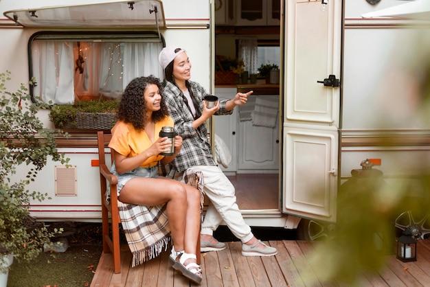 Glückliche freundinnen und wohnmobil