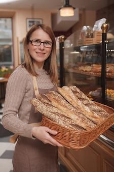 Glückliche freundliche bäckerin, die nach vorne lächelt und brotkorb in ihrem café trägt