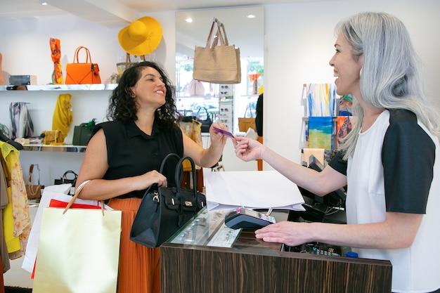 Glückliche freundliche kassiererin, die dem kunden nach der zahlung eine kreditkarte gibt, sich für den kauf bedankt und lächelt. mittlerer schuss. einkaufskonzept