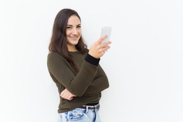 Glückliche freundliche schönheit, die mobiltelefon hält