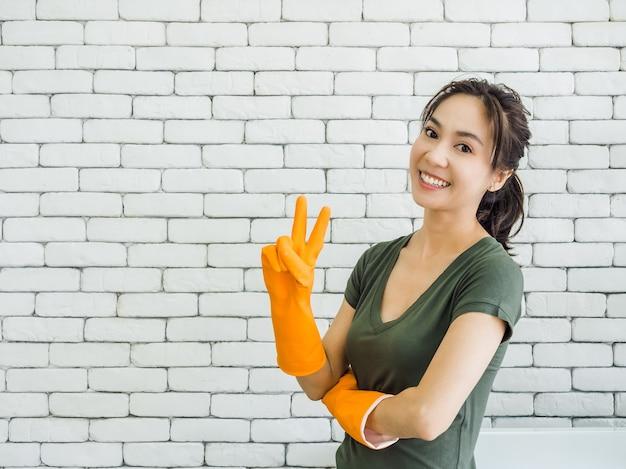 Glückliche fröhlich lächelnde asiatische frau, hausfrau, die orange gummihandschuhe zeigt, die zwei finger zeigen, siegeszeichen nahe waschmaschine auf weißer backsteinmauer