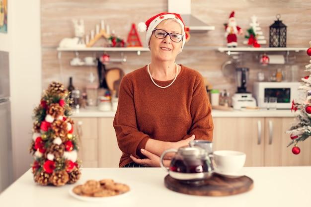 Glückliche fröhliche ältere frau, die weihnachten feiert