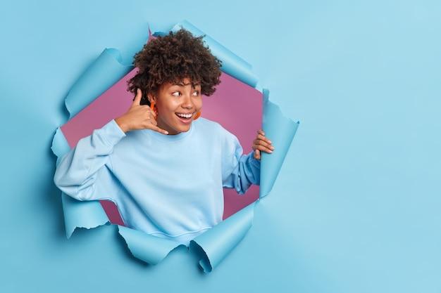 Glückliche fröhliche afroamerikanische frau macht mich anrufen geste schaut mit interesse weg lächeln breit gekleidet in lässigen pullover posen in zerrissenem papierloch der blauen wand