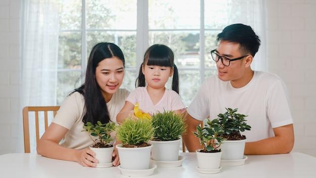 Glückliche fröhliche asiatische familie vater, mutter und tochter bewässerungspflanze im garten nahe fenster am haus