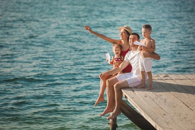 Glückliche fröhliche familie am pier nahe dem wasser, das spaß hat. entzückende kinder, die mit ihren eltern spielen