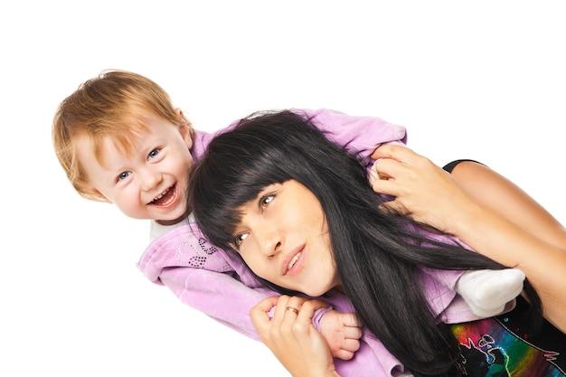 Glückliche fröhliche familie. mutter hält ihr baby isoliert über weiß