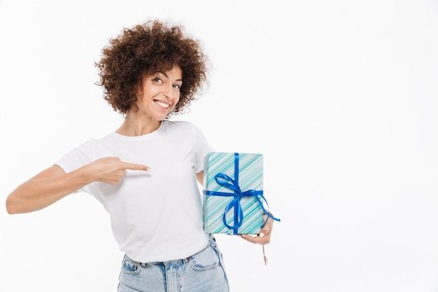 Glückliche fröhliche frau, die finger auf eine geschenkbox zeigt