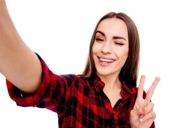 Glückliche fröhliche frau, die v-zeichen zeigt und zwinkert, während selfie macht