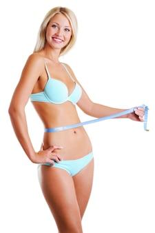 Glückliche fröhliche frau mit einem schönheit schlanken körper misst die taille mit maßband. seitenansicht. auf weiß isoliert