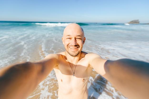Glückliche fröhliche freudige lächelnde männliche person, die selfie im meer unter sonnenstrahlen macht. frohes mann im urlaub nach dem schwimmen im ozean, der am strand mit wellen steht und über kamera lacht. linsenverzerrung.