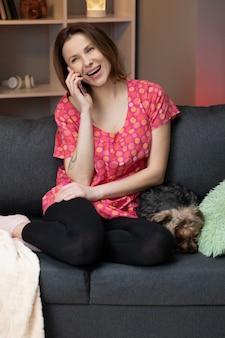 Glückliche fröhliche junge frau, die zu hause am telefon spricht. lächelnde frau, die anrufanruf durch handy macht, das auf sofa sitzt. schöne dame, die angenehmes lustiges gespräch spricht, das durch handy spricht.