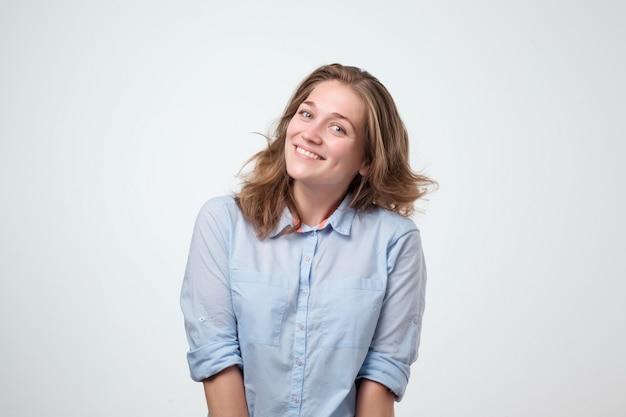 Glückliche fröhliche junge frau im blauen hemd, das über lustigen witz lacht.