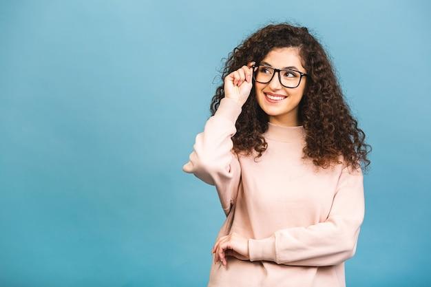 Glückliche fröhliche junge frau mit lockigem haar, die sich über positive nachrichten oder geburtstagsgeschenk freut, mit freudigem und charmantem lächeln.