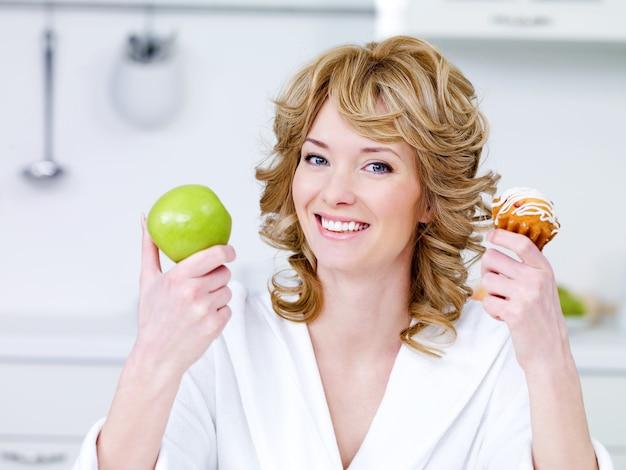 Glückliche fröhliche junge schöne frau mit grünem apfel und süßem kuchen, der in der küche sitzt