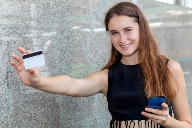 Glückliche fröhliche kaukasische frau, die online mit einer kreditkarte und einer smartphone-anwendung kauft.