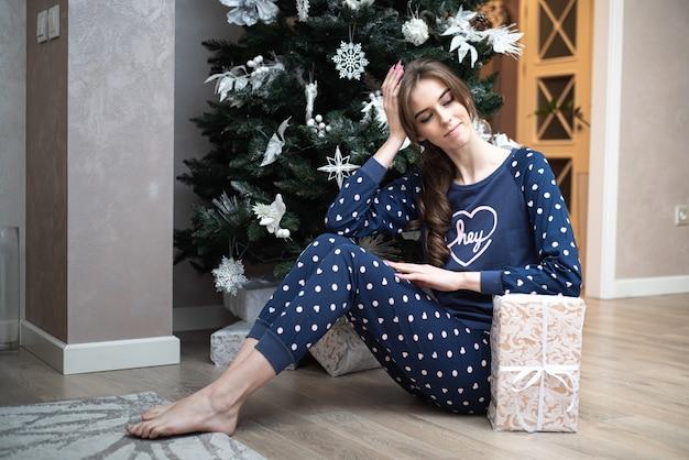 Glückliche fröhliche lächelnde frau im pyjama und spaß beim lachen und vorbereiten für weihnachten