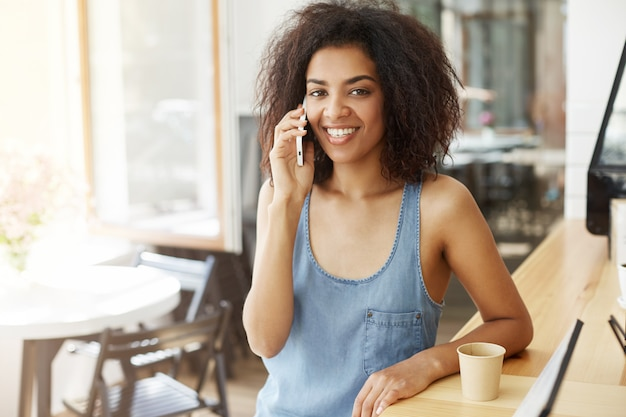 Glückliche fröhliche schöne afrikanische frau lächelnd am telefon sitzen im café.