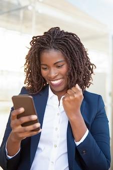 Glückliche frohe geschäftsfrau, die mobiltelefon hält