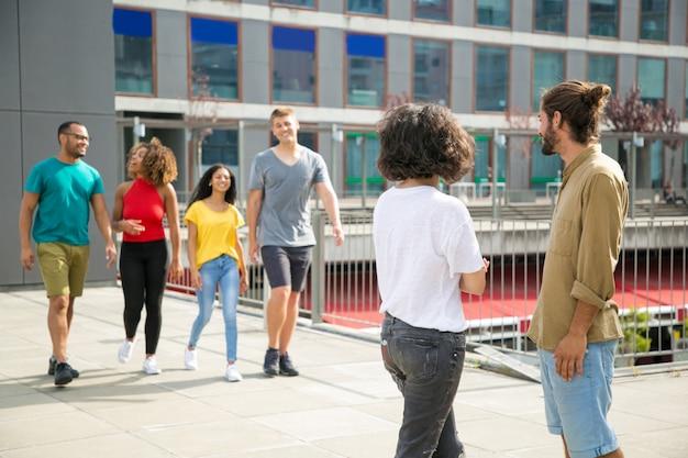Glückliche frohe multiethnische freunde, die sich draußen treffen