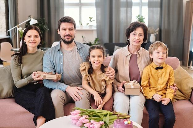 Glückliche fünfköpfige familie, die in reihe auf einer großen, weichen, bequemen couch im wohnzimmer sitzt und sie während der frühlingsferien ansieht