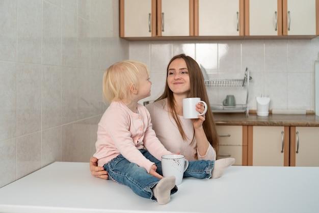 Glückliche fürsorgliche mutter und kleines blondes mädchen frühstücken in der küche.