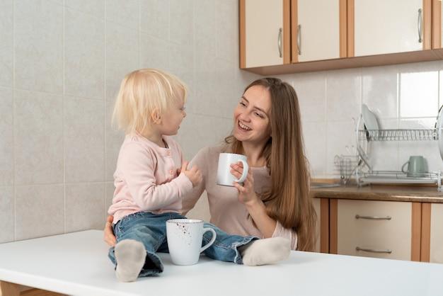 Glückliche fürsorgliche mutter und kleines blondes mädchen trinken tee in der küche. familienfrühstück.