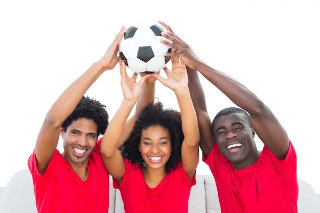 Glückliche fußballfane im roten haltenen ball