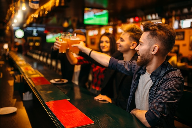 Glückliche fußballfans hoben ihre gläser mit bier an der theke in einer sportkneipe, siegesfeier