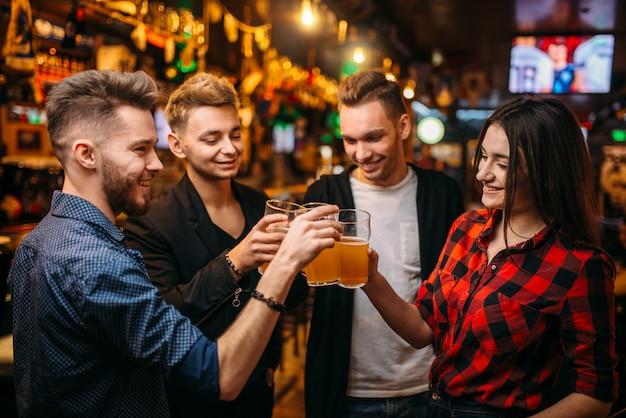 Glückliche fußballfans hoben ihre gläser mit bier