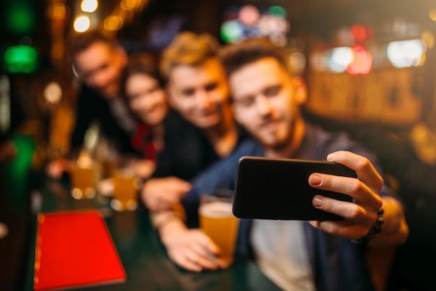 Glückliche fußballfans machen selfie an der theke
